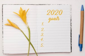 Top view of open notebook with wirtten 2020 goals. Yellow flower